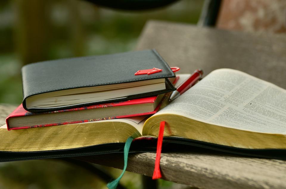 Sur une table une bible avec des carnets des notes ainsi un stylo